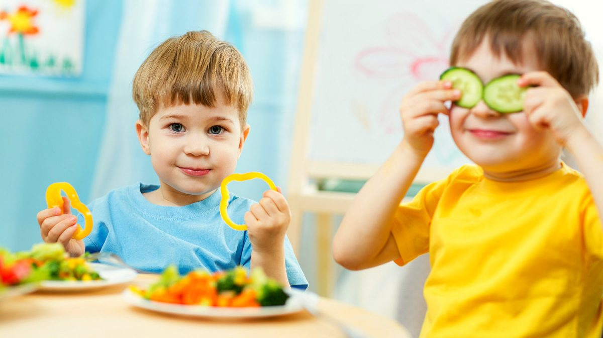 two young boys eating vegetables
