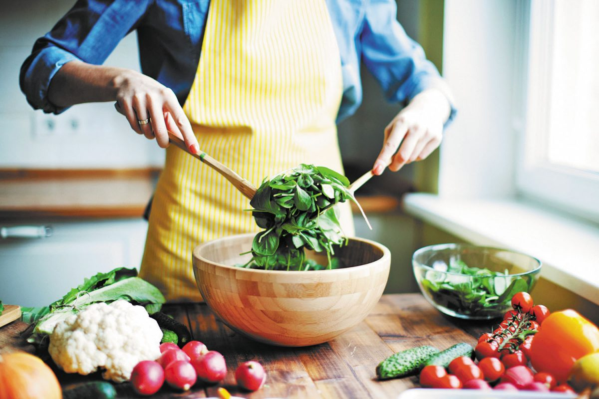a woman mixing salad in a wooden bowl