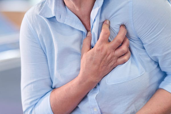 a woman clenching her chest while being in pain
