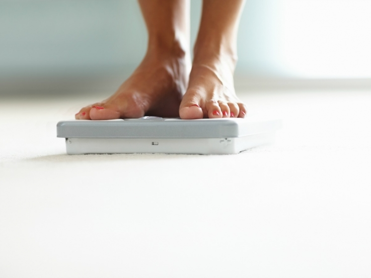 a person messuring bodyweight on a weighing scale