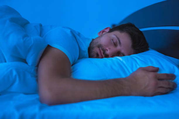 a man sleeping on his bed with a smie