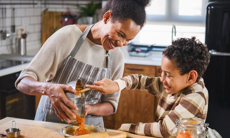 a mother and her child happily preparing a pumpkin pie
